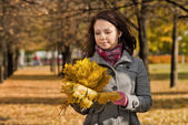 Girl with autumnal leafs in park — Stock Photo