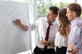 Leader explaining something on whiteboard — Stock Photo
