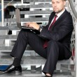 A businessman sitting on stairs smiling with a laptop computer - Foto Stock
