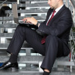 Handsome businessman sitting on the stairs and using his laptop — Stock Photo
