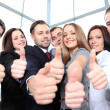 Successful young business showing thumbs up - Foto Stock