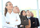 Business team standing in a row at office and looking upwards — Stock Photo