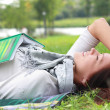 Happy young woman lying on green grass — Stock Photo #20048277