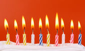 10 lit birthday candles in bright colors with red background — Stock Photo