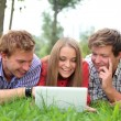 Smiling students with laptop on natural background — Stock Photo