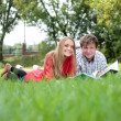 Two students reading the book on a grass in the park — Stock Photo