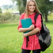 Female student outdoors holding a notebook and smiling — Stock Photo