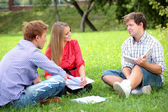 Happy group of students with a notebook smiling outdoors — Stock Photo