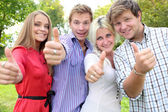 Happy group of students with thumbs up - outdoors — Stock Photo