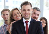 Portrait of a happy young male business leader standing in front of his team — Stock Photo