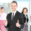 Cheerful business man with team giving you thumbs up — Stock Photo