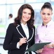 Two business women discussing project and smiling at office - Stock Photo