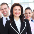 Happy young female business leader standing in front of her team — Stock Photo #25370641