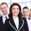 Happy young female business leader standing in front of her team — Stock Photo