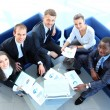 Stock Photo: Top view of working business group sitting at table during corporate meeting