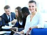 Erfolgreiche geschäftsfrau, die mit ihren mitarbeitern im hintergrund im büro sitzen — Stockfoto