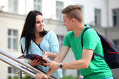 Two students studying with computer notebook outdoors — Stock Photo