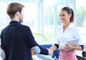 Cheerful businesspeople, or businesswoman and client handshaking — Stock Photo