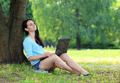 Young women lying on grass in park and using laptop — Stock Photo