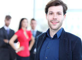 Happy smart business man with team mates discussing in the background — Stock Photo