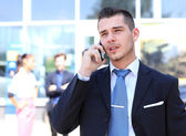 Happy successful young business man talking on cell phone — Stock Photo
