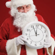 Photo of stunned Santa holding clock showing five minutes to midnight — Stock Photo #35416897