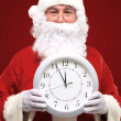 Photo of Santa pointing at clock showing five minutes to midnight — Photo