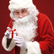 Stock Photo: Photo of happy Santa Claus looking into white giftbox in isolation