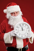 Photo of stunned Santa holding clock showing five minutes to midnight — Stock Photo