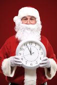 Photo of Santa pointing at clock showing five minutes to midnight — ストック写真