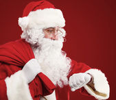 Portrait of Santa Claus with a bag of presents and looking at his watch. Christmas. — Stock Photo
