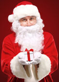 Photo of kind Santa Claus giving xmas present and looking at camera — Stock Photo