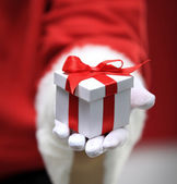 Photo of Santa Claus gloved hands holding white giftbox — Stock Photo