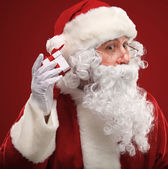Photo of Santa Claus holding red giftbox by his ear — Stock Photo