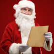 Portrait of happy Santa Claus holding Christmas letter and looking at camera — Stock Photo #35738389