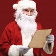 Portrait of happy Santa Claus holding Christmas letter and looking at camera — Stock Photo #35738413