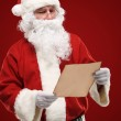 Portrait of happy Santa Claus holding Christmas letter and looking at letter — Stock Photo #35738503