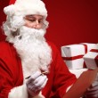 Stock Photo: SantClaus looking at envelope