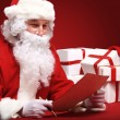 Santa Claus looking at envelope — Stock Photo