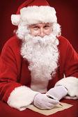 Santa Claus looking at envelope — Stock Photo