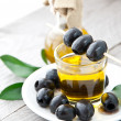 Plate with olives and a bottle of olive oil on a wooden background — Stock Photo