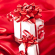 Stock Photo: Small gifts with red bow on red background