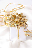 Gold ribbon gift with festive holiday background — Stock Photo