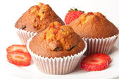 Strawberry muffin on a white plate with a fresh strawberry — Stock Photo