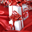 Small gifts with red bow on red background — Stock Photo