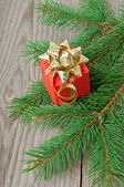 Rote geschenk und zweige eine tanne auf einem hölzernen hintergrund — Stockfoto