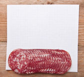 Paper records and pieces of sausage — Stock Photo