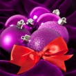 Violet Christmas balls on a violet background — Stock fotografie