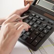 Woman's hand with a pen, calculator and the financial report — Foto Stock
