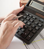 Woman's hand with a pen, calculator and the financial report — Stock Photo